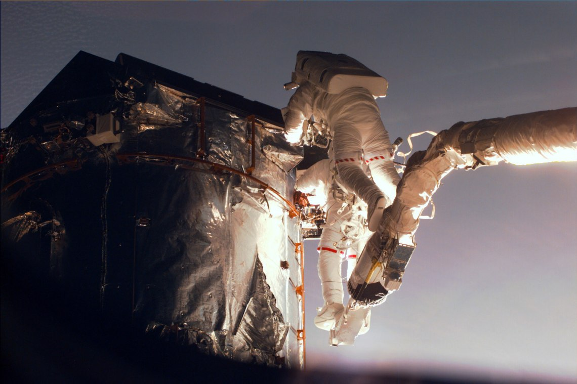 Gregory Harbaugh (solid stripe on EMU) uses the remote manipulator system (RMS) as a cherry-picker device to service Hubble. In cooperation with Joseph Tanner, nearby, Harbaugh is in the process of replacing the Magnetic Sensing System (MSS) protective caps with new, permanent covers. Credit: NASA