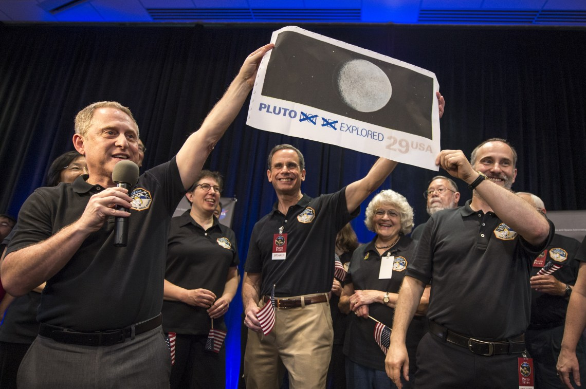 New Horizons Principal Investigator Alan Stern of Southwest Research Institute (SwRI), Boulder, CO., left, Johns Hopkins University Applied Physics Laboratory (APL) Director Ralph Semmel, center, and New Horizons Co-Investigator Will Grundy Lowell Observatory hold a print of an U.S. stamp with their suggested update since the New Horizons spacecraft has explored Pluto, Tuesday, July 14, 2015 at the Johns Hopkins University Applied Physics Laboratory (APL) in Laurel, Maryland. Credit: NASA/Bill Ingalls