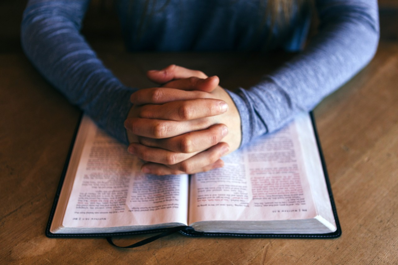 person praying with hands on a Bible