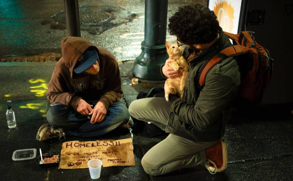 homeless man with a man helping him