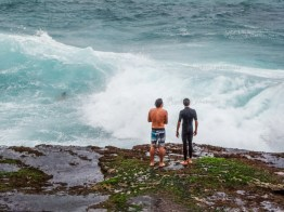 These three boys do not seem to be afraid to be crushed against the rocks, Bondai beach