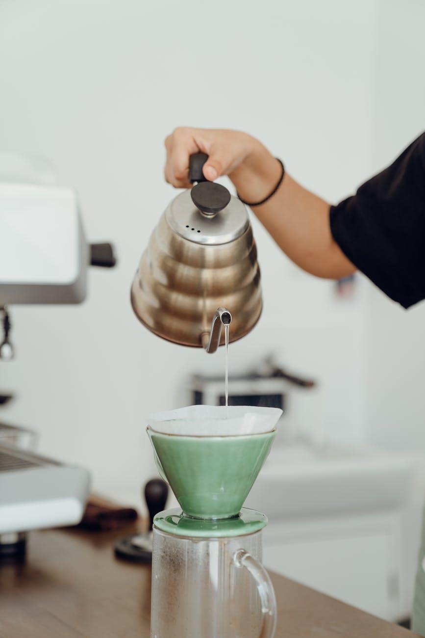 crop woman preparing hot coffee in kitchen