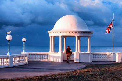 Luminous blue storm clouds over the white classic dome of the King George V Colonnade at Bexhill on Sea
