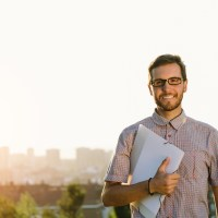 Successful professional casual man walking outside against city background. Happy smart looking person holding folder and smiling.