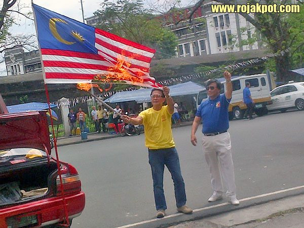 Retired police officer, Abner Afuang, burning the Malaysian frag on the 6th of March 2013.