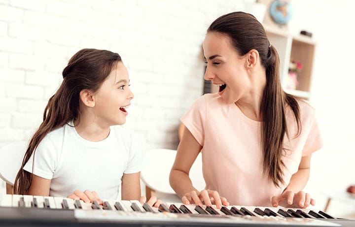 mum girl playing piano together