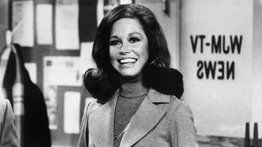 (Original Caption) Still from The Mary Tyler Moore Show showing Moore standing, smiling, inside of the WJM newsroom. Moore is shown from the waist-up, holding a cup of coffee, circa 1975.