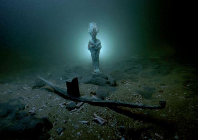Statuette d'Osiris en bronze et barque votive en plomb posées sur les fonds sous-marins de la baie d'Aboukir. Thônis-Héracléion, Egypte VIè - IIè siècles av. J.-C. / Photo : Christoph Gerigk © Franck Goddio/Hilti Foundation