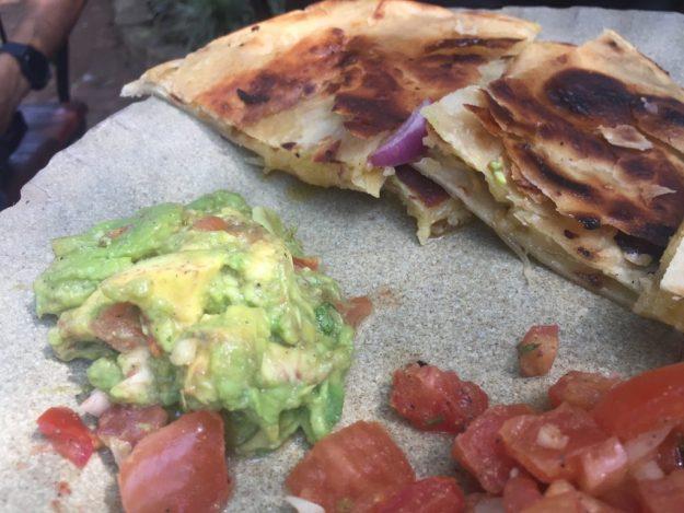 Repas Kenya « tsavo taco » qui est une galette garnie de poulet mariné accompagné de haricots rouge, d'une petite salade de tomates ainsi que de guacamole