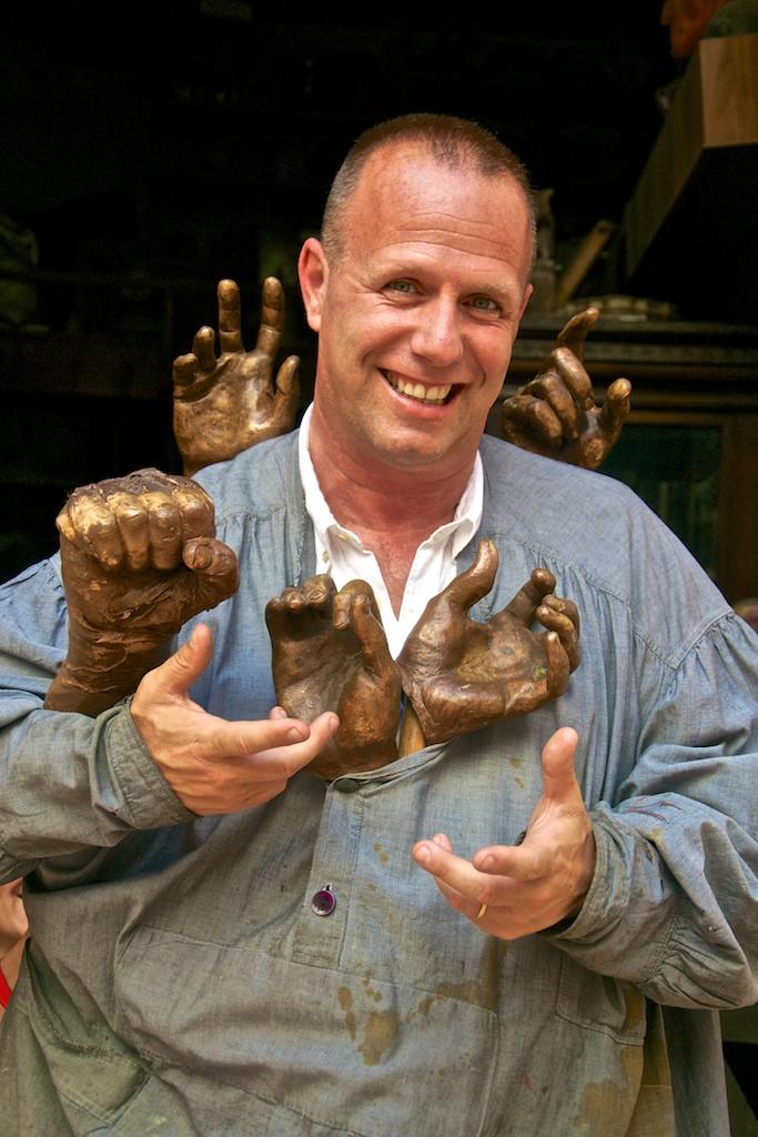 Uomo cesellatore con camicia grigia da lavoro, sorridente e circondato dalle mani in bronzo che egli stesso crea