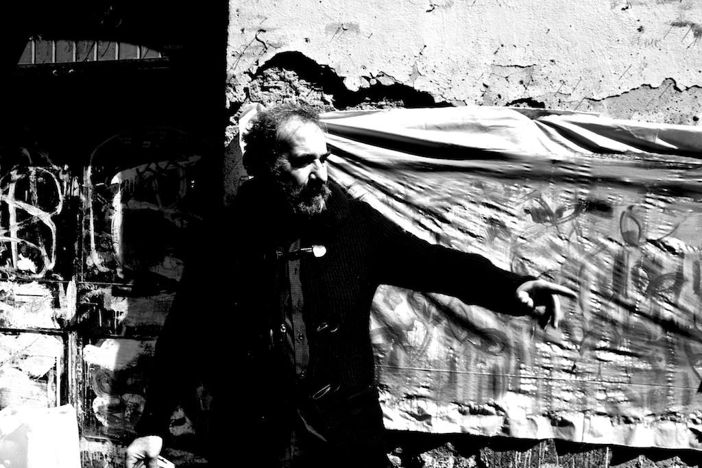 Uomo barbuto con alle spalle un telo inchiodato al muro sul quale ha dipinto segni informali. Guarda verso sinistra e indica con il braccio qualcosa in basso.