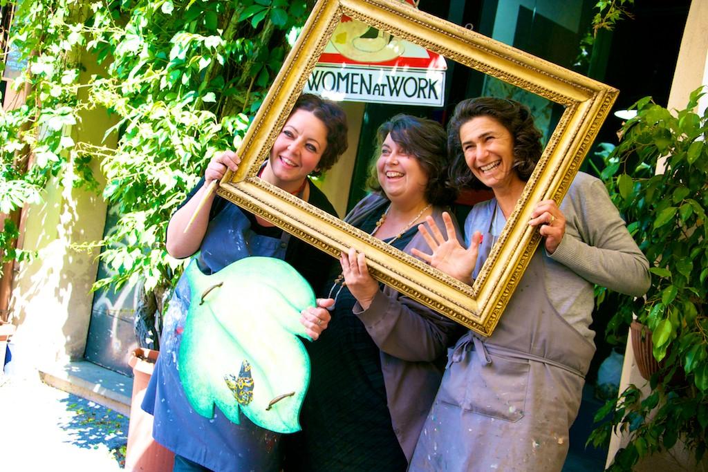 donne restauratrici, con camici da lavoro, che sorridono dentro una cornice dorata. Sullo sfondo dell'immagine il cartello stradale triangolare con soprascritte women at work.