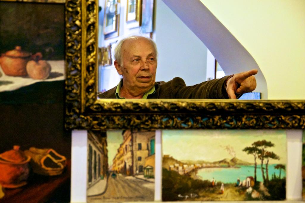 Uomo anziano riflesso nello specchio che indica con l'indice i suoi quadri appesi in un bar
