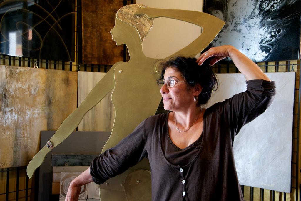 Donna in posa imita la sua scultura di legno dipinta in oro.