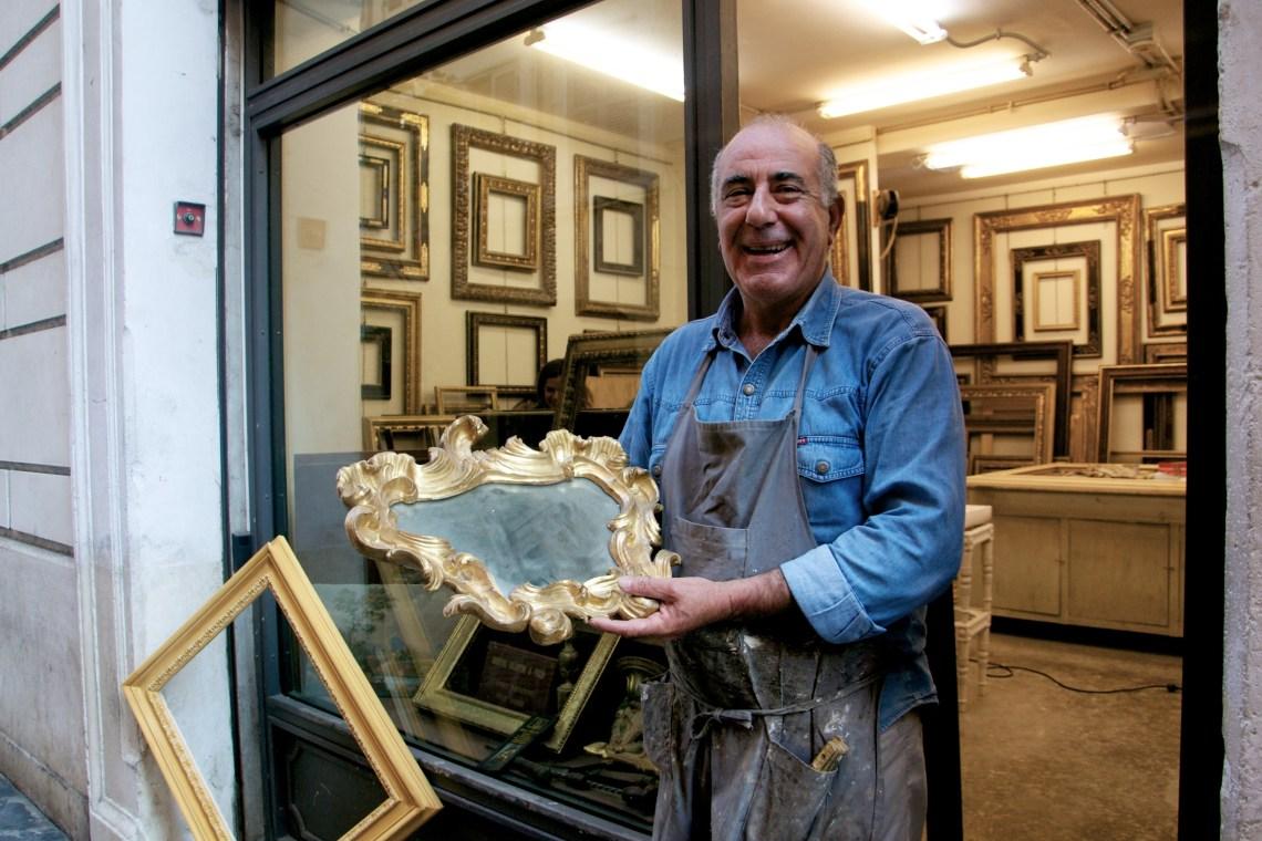 Uomo fuori dalla sua bottega mostra sorridente una sua cornice dorata su uno specchio.