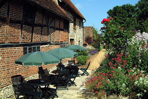 Garden with tables and parasols along a path, with an old brick-built house on the left