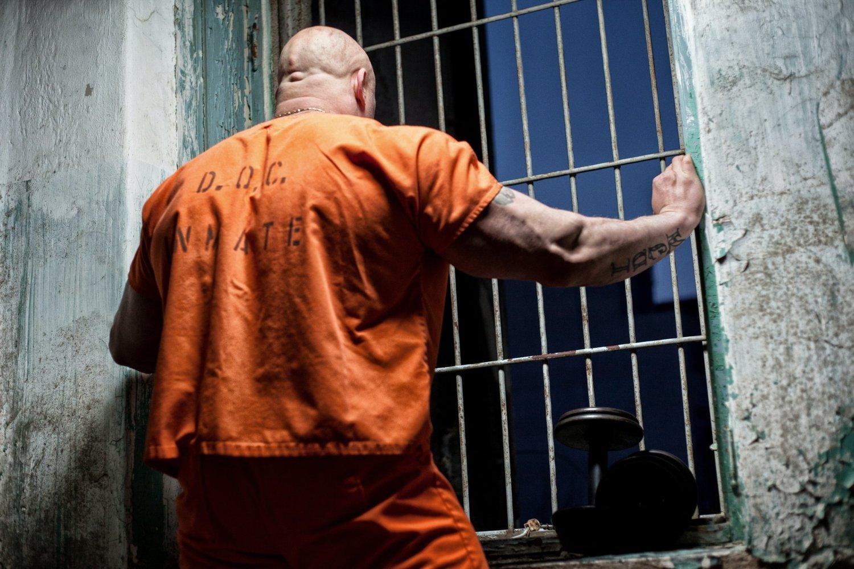 prisoner with hands on bars