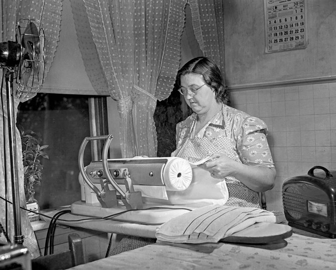 Mrs. Robert Bacon, farm wife, with some of herelectric appliances - fan, ironer, radio - utilizing energy fromthe TVA power grid. Knox County, Tennessee. 1942.