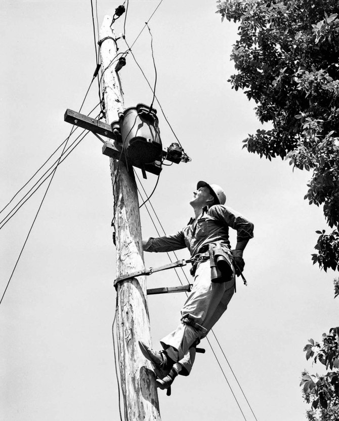 Julien H. Case repairing the transformer that brings TVA electricity to his farm. Lauderdale County, Alabama. 1942.