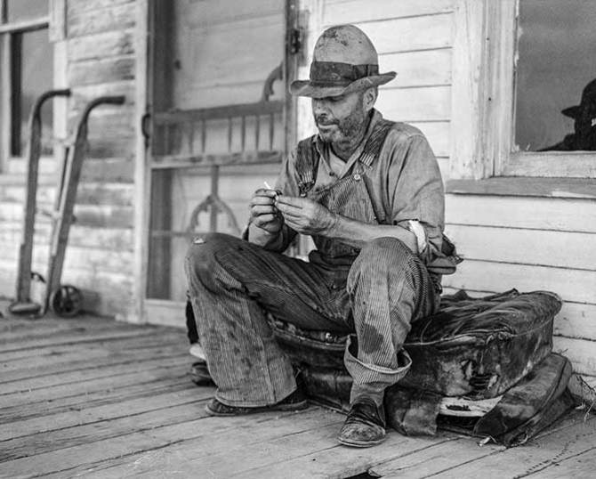 Waiting for better times, J. Huffman of Grassy Butte, North Dakota, sits in front of his closed store.1936