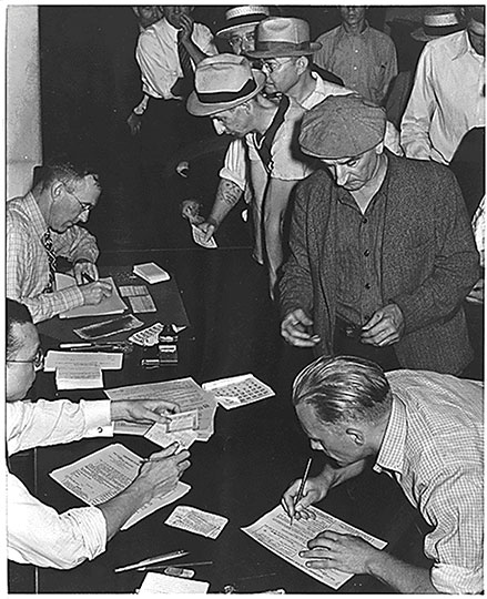 Unemployed workers signing up for unemployment benefits following passage of the Social Security Act. (NARA)