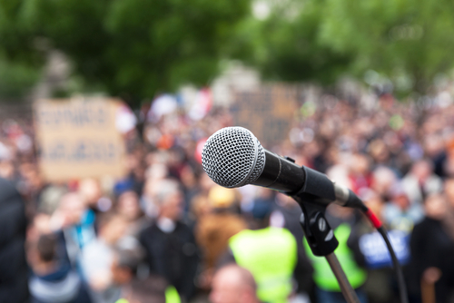 A crowd assembled to protest. The crowd is blurred. In the foreground of the picture, in focus, is a microphone.