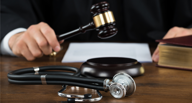 Judge in position to bang a gavel, with a piece of paper and a stethoscope in front of him.