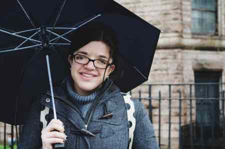 Photo of Ariel Henley in a gray jacket, smiling and holding a black umbrella.