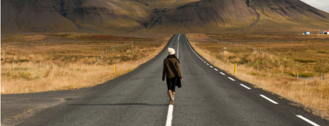 A female presenting person in a white hat, dark brown jacket, and light brown boots, walking down a road alone toward a mountain range, surrounded by wide open space with browned grass.