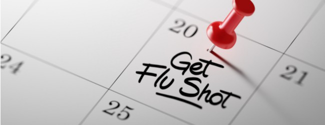 """Image of a calendar with the words """"get flu shot"""" written down in the box for the 20th. There is a red push pin on top of it."""