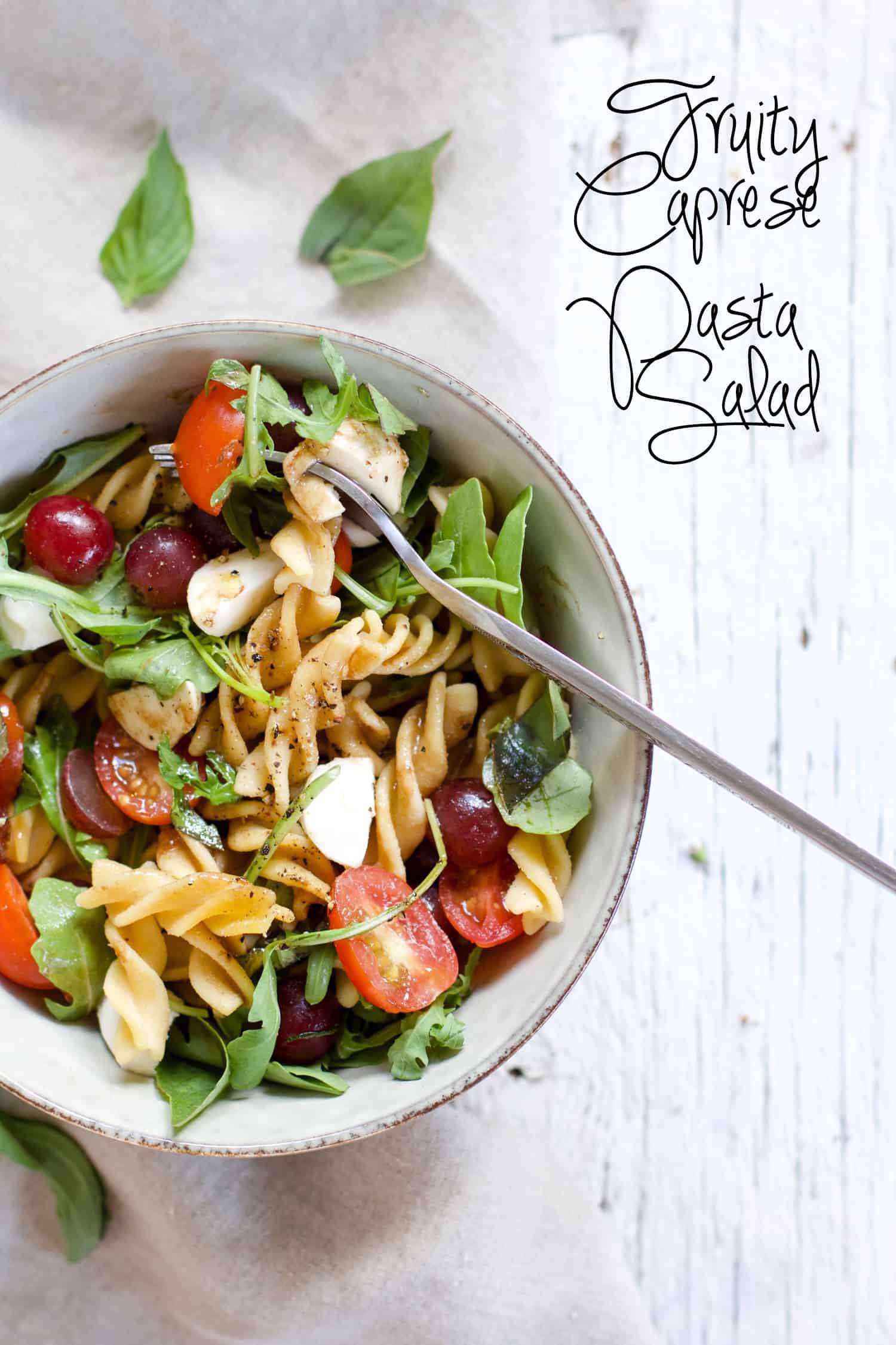 Fruity Caprese Pasta Salad - A fruity twist in the classic caprese salad! Summery, refreshing, perfect for picnics. Grapes, grape tomatoes, fresh mozzarrella, arugula, basil, olive oil & balsamic | rootsandradishes.com