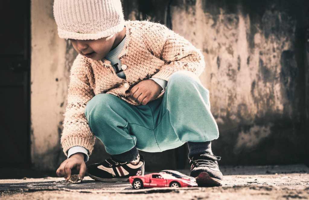 Nene jugando a carreras con su cochecito rojo