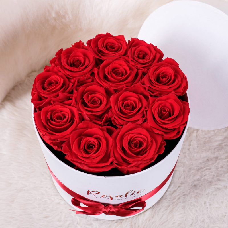 box tondo con 12 rose rosse stabilizzate su sedia bianca