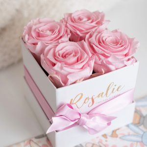 quattro rose stabilizzate di color rosa in scatola quadrata con nastro rosa con fiocco, visto dall'alto. Su tavolo bianco.