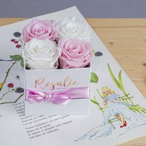 scatola quadrata con 2 rose rosa e 2 rose bianche. Con nastro di color rosa. Appoggiata su libro di fiabe, il tutto su tavolo di legno chiaro.