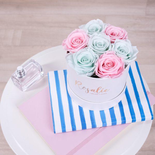 scatola tonda con rose stabilizzate di color rosa e menta su quaderni accanto a profumo