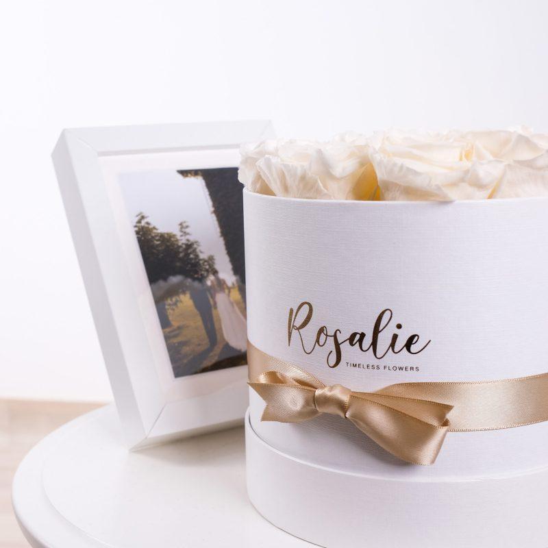 box tondo con rose stabilizzate color bianco panna e nastro dorato con accanto cornice con sposi