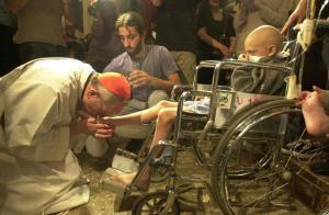 Il cardinale Bergoglio, ora Papa Francesco, in una foto d'archivio, bacia i piedi di un bambino malato