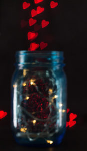Blue mason jar with fairy lights and a red heart bokeh background. | https://www.roseclearfield.com