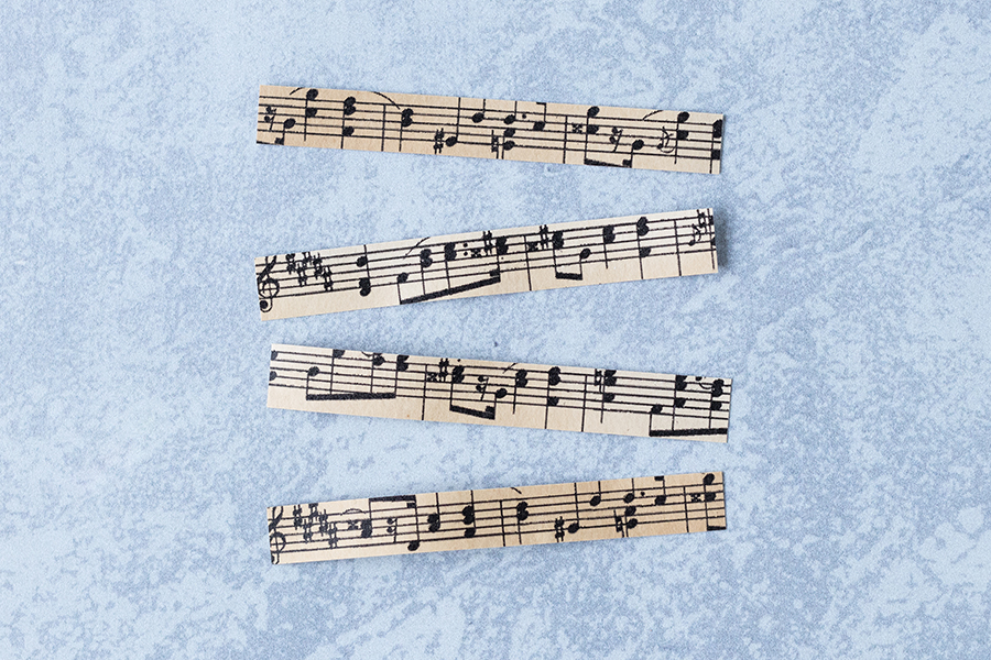 Antique sheet music cut into strips for DIY clothespin magnets. #sheetmusiccraft #DIY #clothespins | https://www.roseclearfield.com