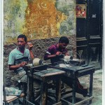 on a back street in Cairo, two men sit at rough workbenches and hammer out cloisonne vases