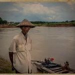 man in palm leaf hat stands on the banks of the Irrawaddy River
