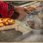 a gypsy passes burning incense to a customer