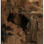 Berber man in djellaba stands in front of cave home entrance