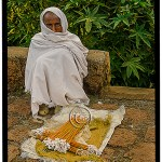 Man huddled in white shawl sells candles before mass in stone churches of Lalibela