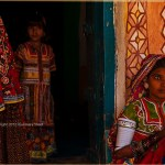Rabari Girl in Gujarati village sits by doorway