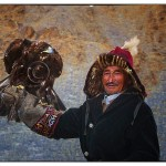 Kazakh Eagle Hunter holding eagle with mountain background
