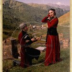 Georgian couple in traditional costume posed above village in Caucasus Mountains