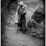 b/w photo of Ethiopia woman walking in canyon with a staff