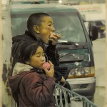 brother and sister munch on apples in Bayan-Olgii Market, Mongolia